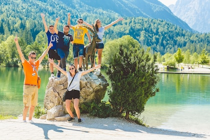 Tour group poses around large rock on the shore of the Soca River