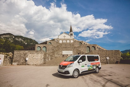 Transportation van sits in front of old stone church in Slovenia