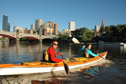 People in tandem kayak paddle on canal in Melbourne