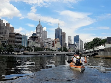 People paddling down canal with view of Melbourne cityscape