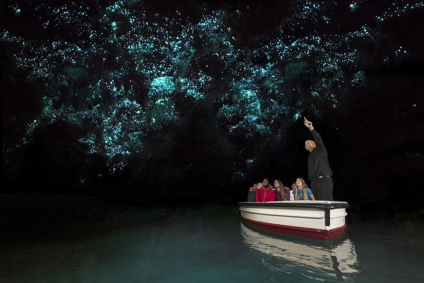 Show item 3 of 7. Boat with tourists paases under glowworms at Waitomo Glowworm Caves