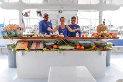 Tour guides aboard catamaran showing custom buffet