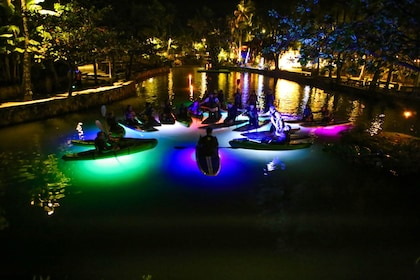 Colorfully lit pool with group of paddleboarders