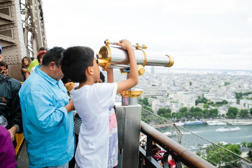 Charger l'élément 4 sur 7. Kid looking through a viewfinder from the Eiffel Tower in Paris
