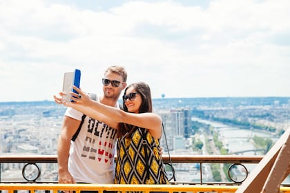 Couple taking a selfie on the Eiffel Tower in Paris