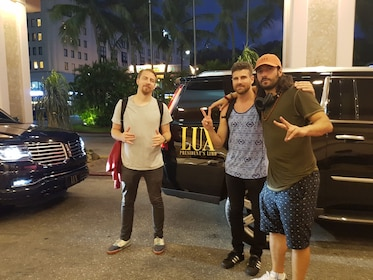 Group of mean pose outside limousine SUV at night in Guam