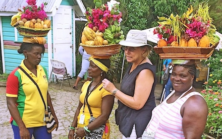 Tourist with locals carrying fruit baskets on the top of their heads in Grenada