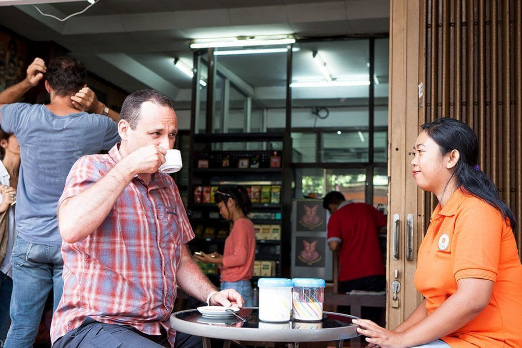 Two visitors drink coffee outside cafe in Denpasar city