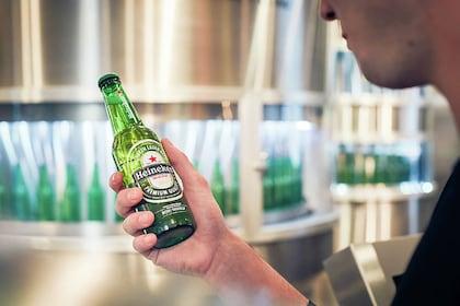 Guest holding a Heineken® bottle at the Heineken® Experience tour in Amsterdam