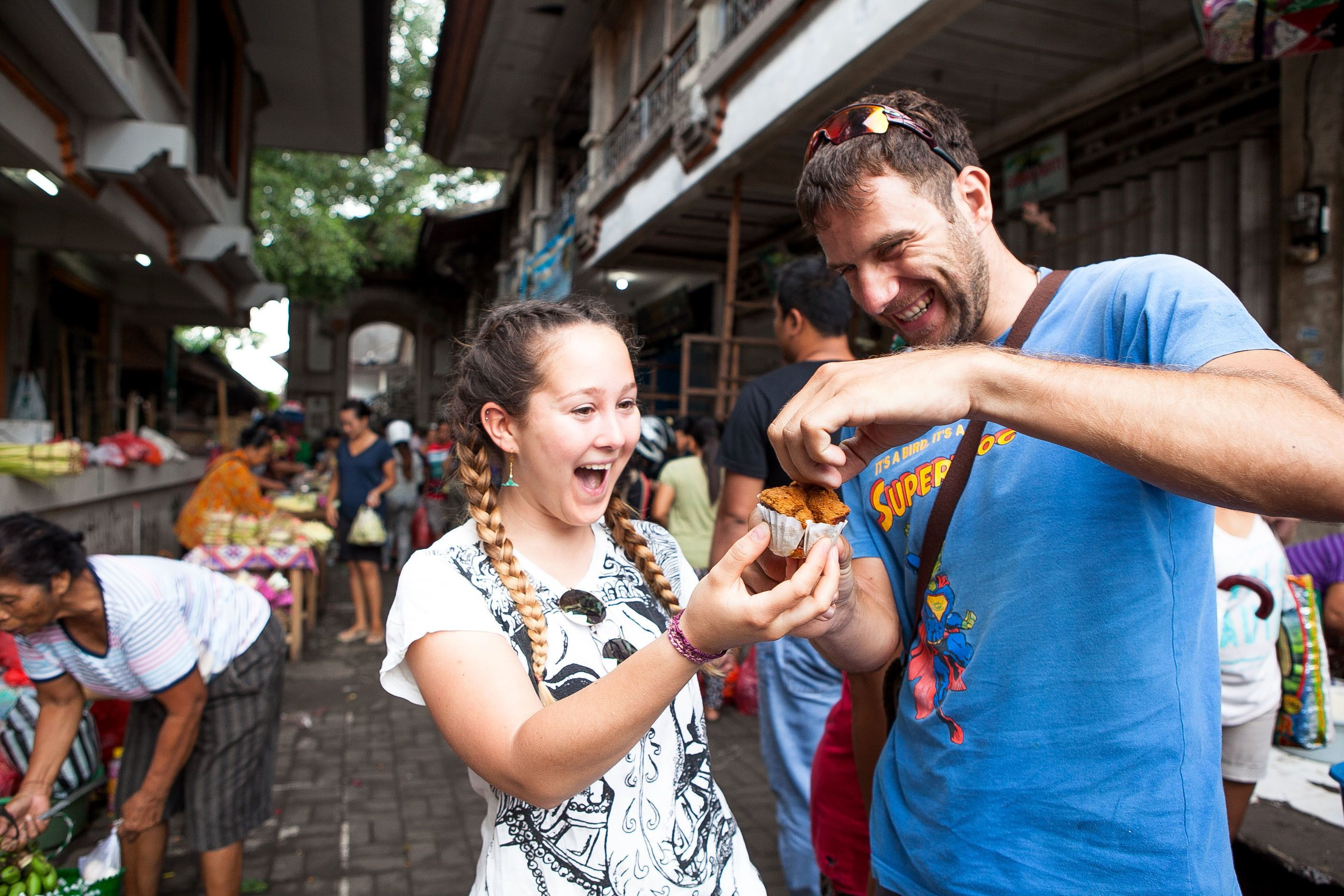 Two people enthusiastically eating food on the streets of Indonesia