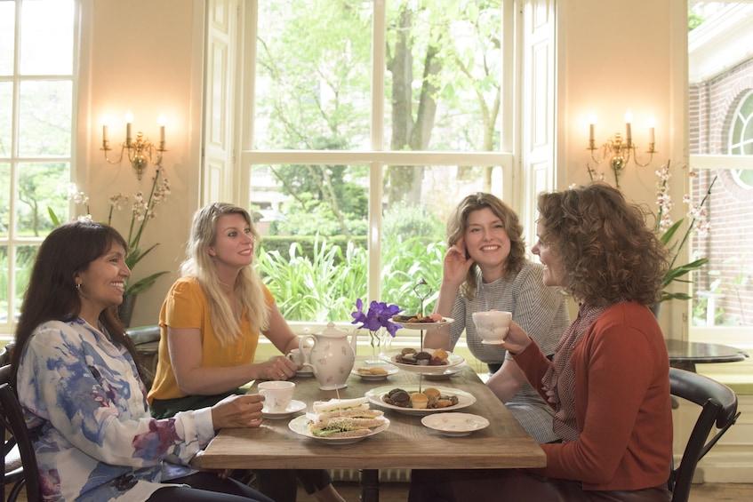 Åpne bilde 5 av 5. Women enjoying tea time at Cromhouthuis museum in Amsterdam