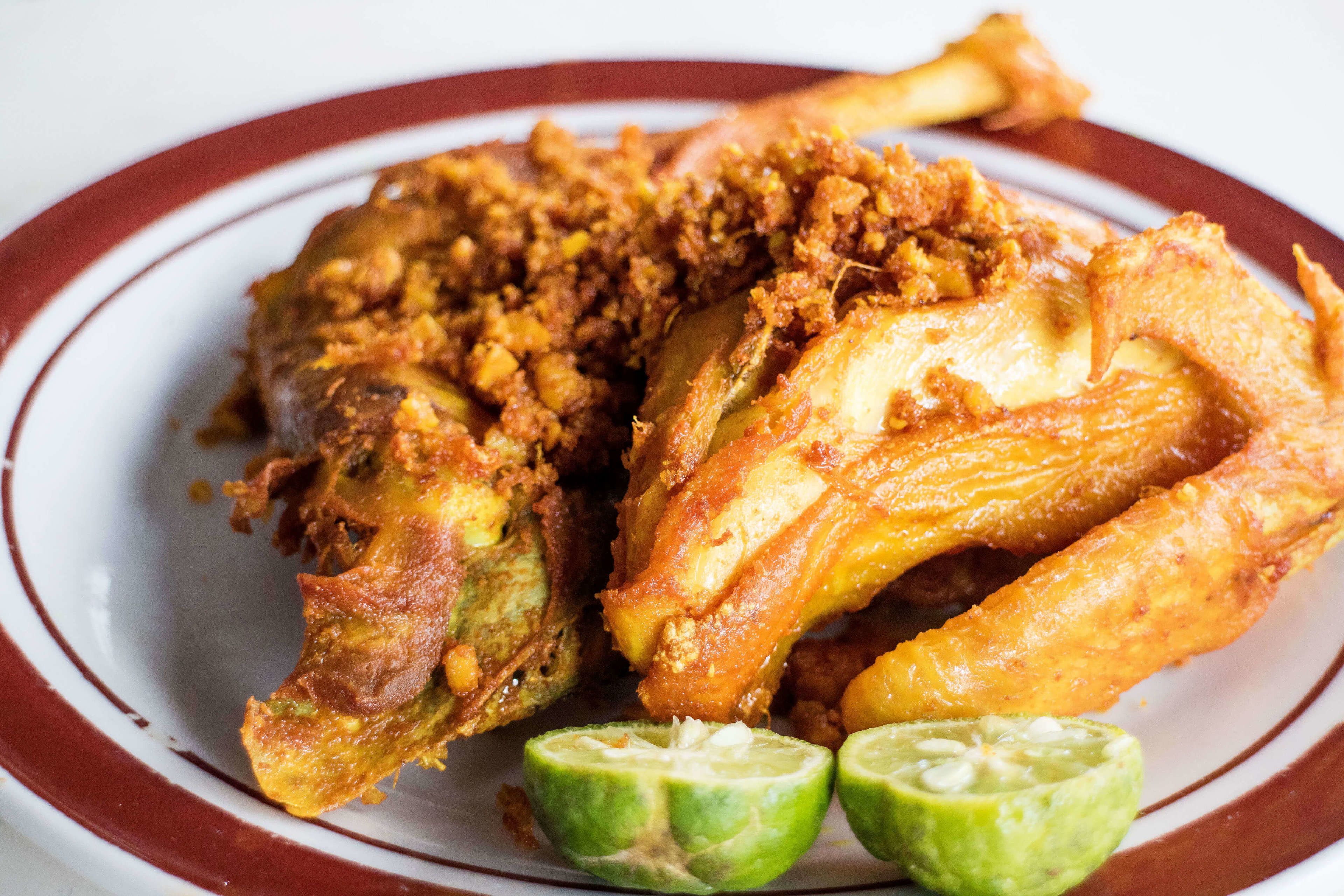 Fried chicken and limes on a plate on the Kota Tua Foodie Tour