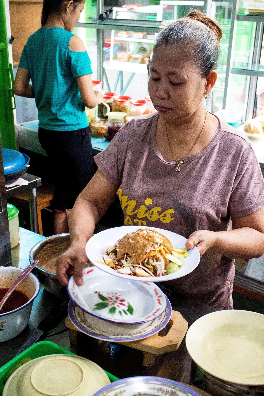 Two women preparing traditional dishes on the Kota Tua Foodie Tour