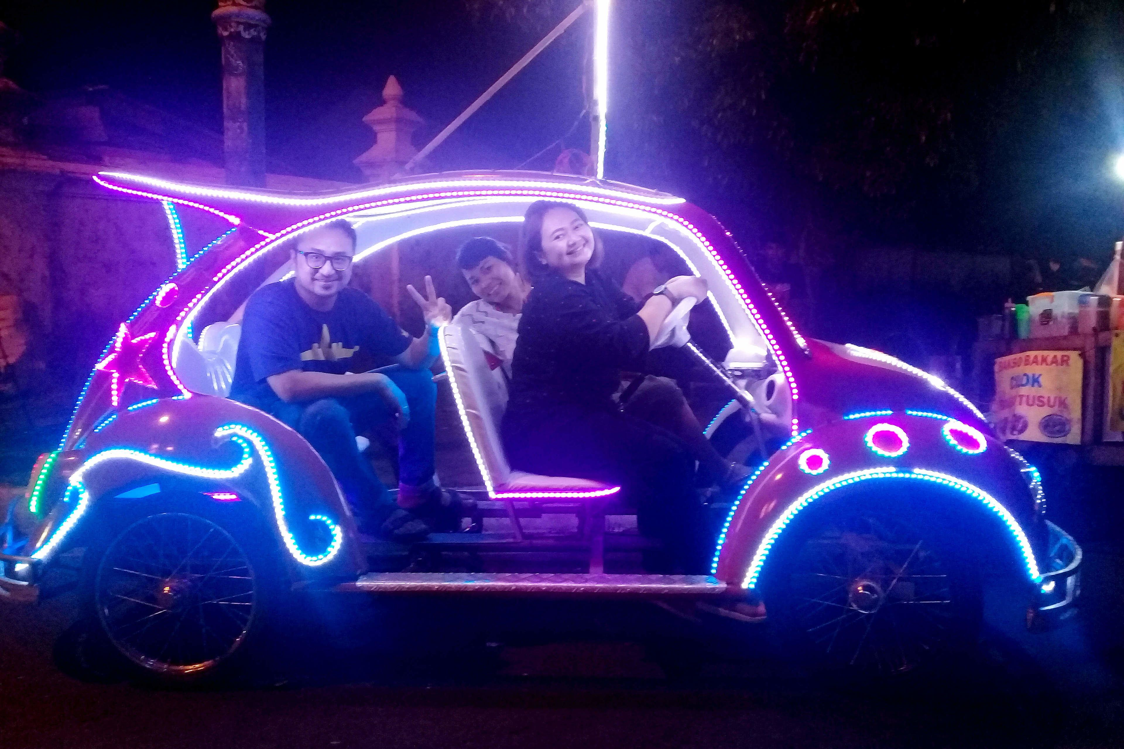 Tour group sitting in a car with lights on the Yogyakarta Night Food Tour