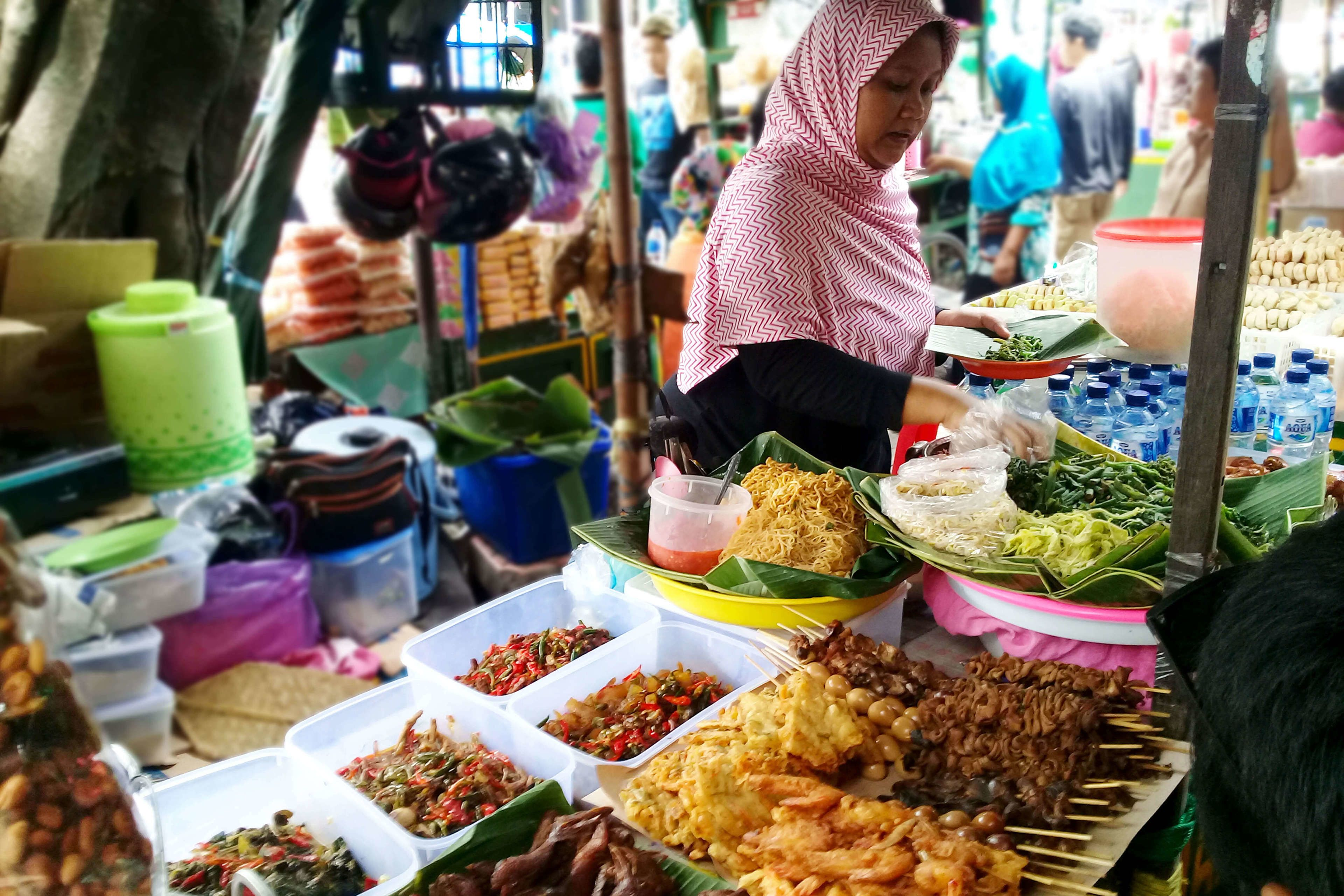 Woman selling food at an open air market in Indonesia