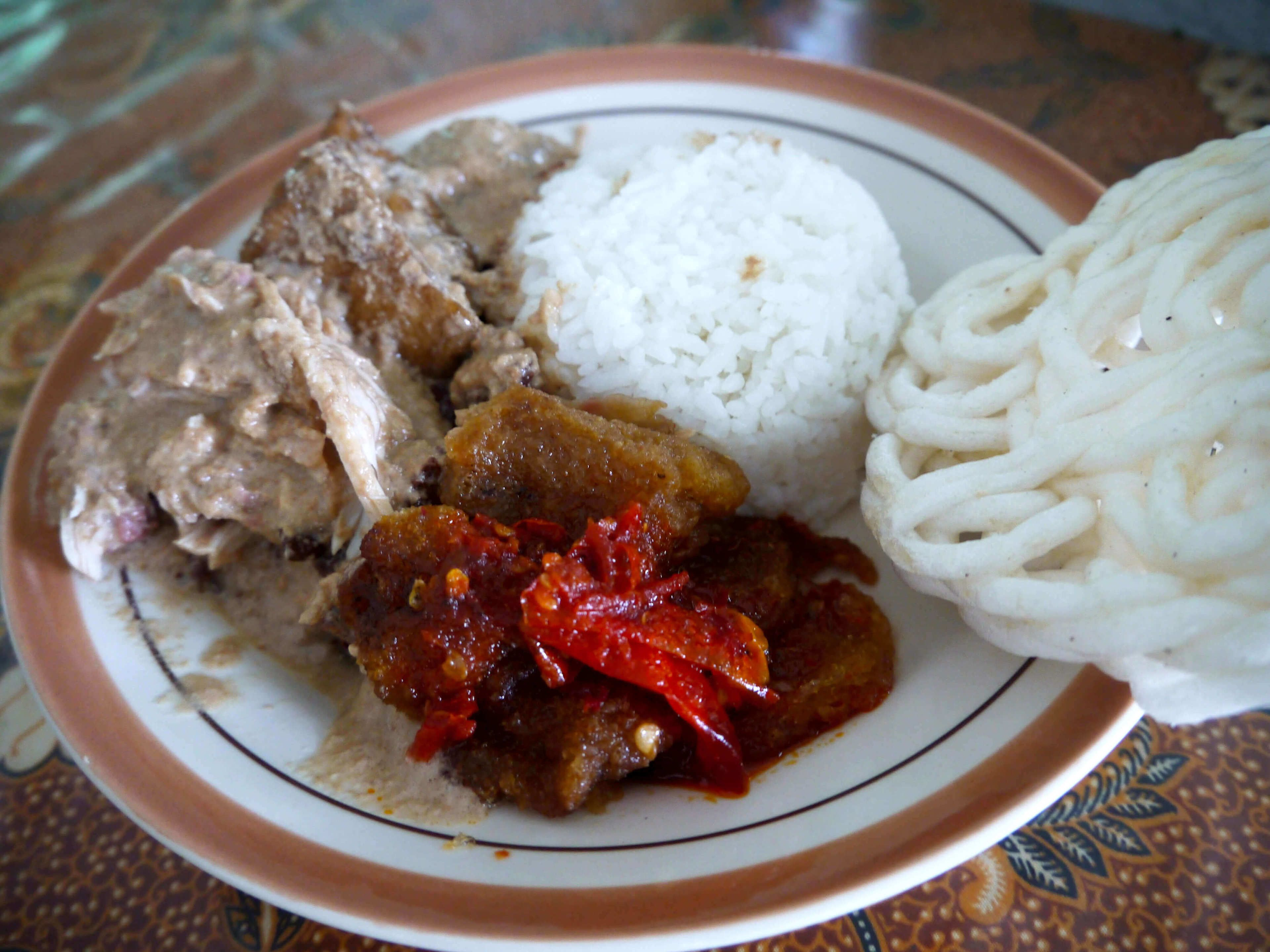 An Indonesian dish of meat in gravy, rice. noodles, and chilies