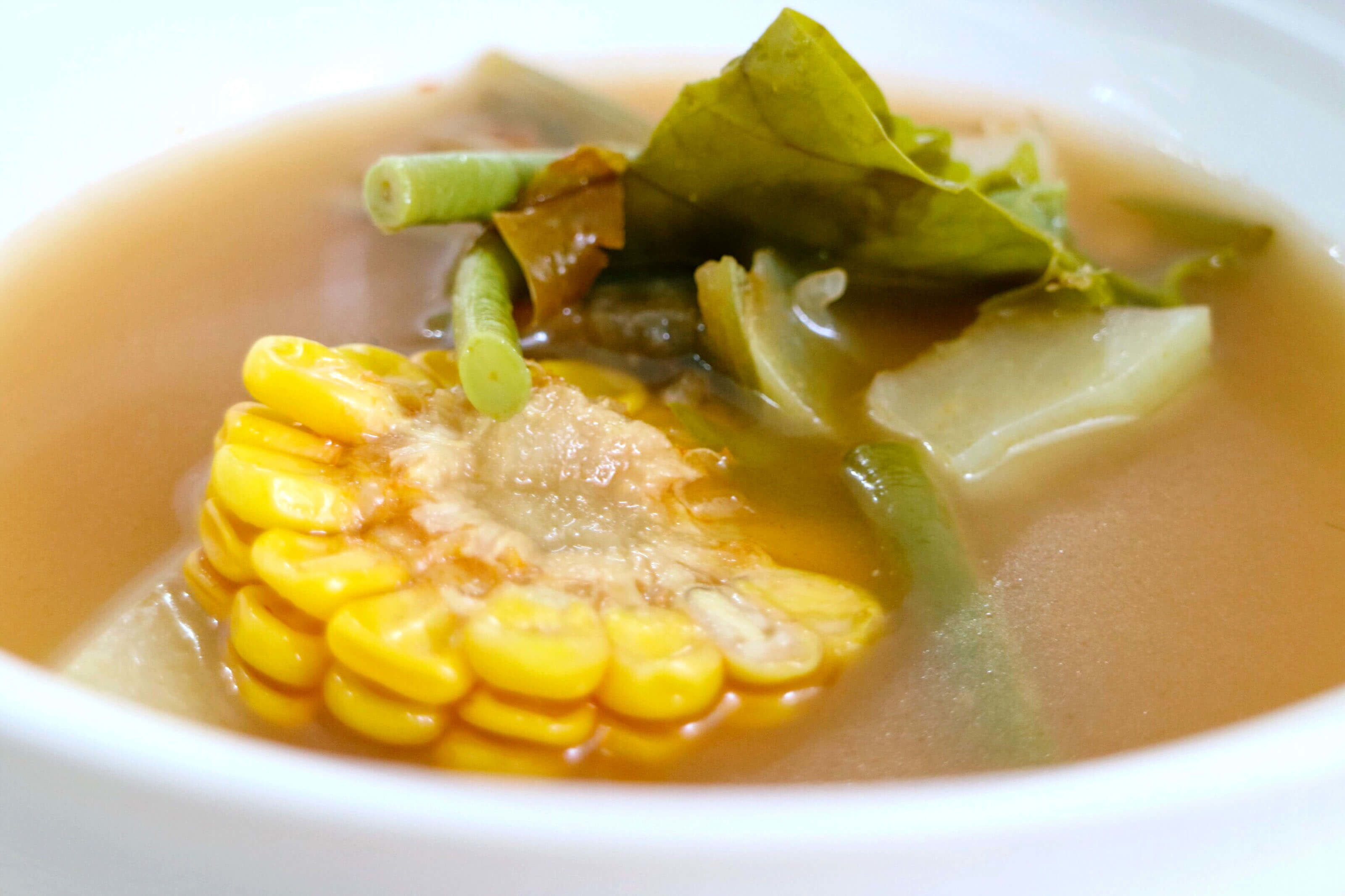 An Indonesian dish of corn on the cob, beans, and bay leaves in a broth