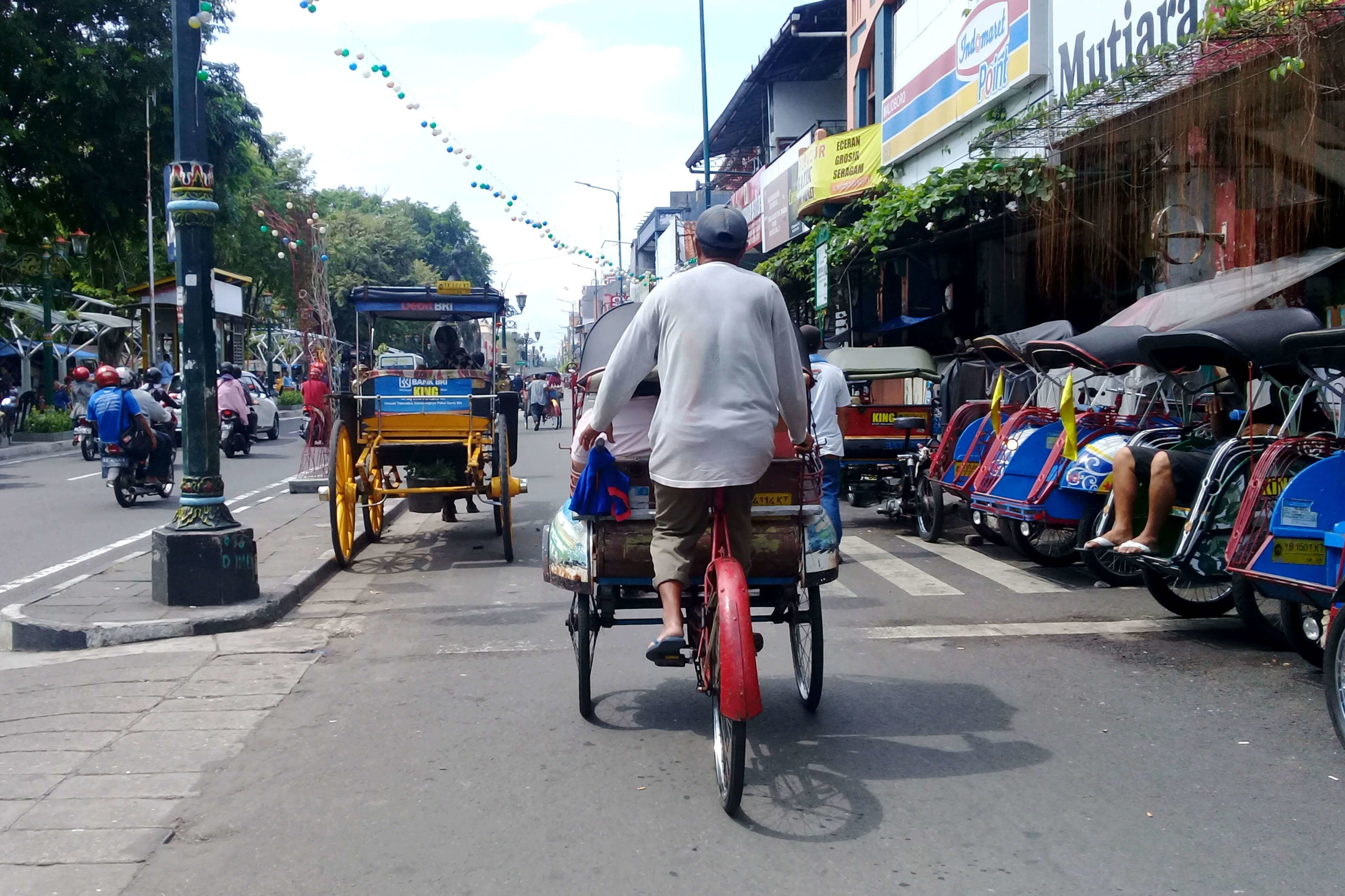 Man on a bike pushes a cart on an Indonesian street
