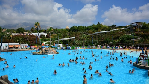 Large group of people wadding in a wave pool at a water park in Barcelona