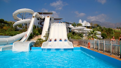 Four people travel down a large water slide into a pool at a water park in Barcelona