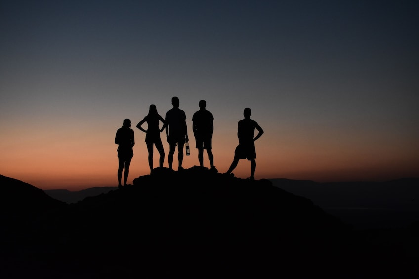 Silhouette of hikers with sunset in the background in Israel