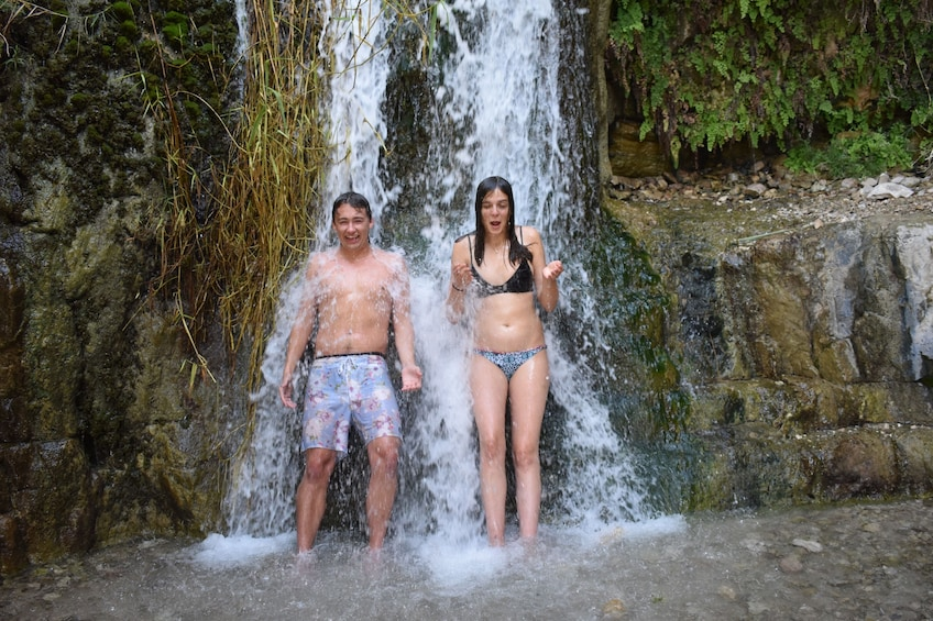 Couple standing under a waterfall in Israel