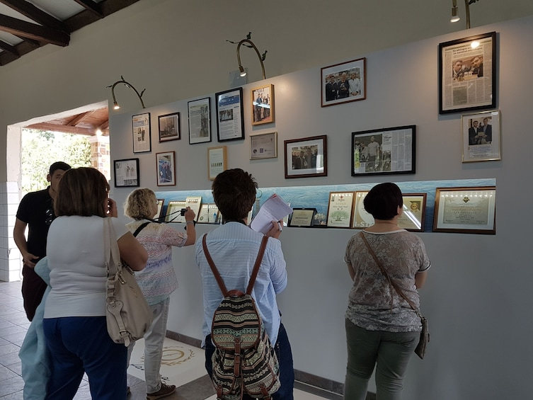 Show item 4 of 4. Tour group looking at pictures on a wall in Corfu