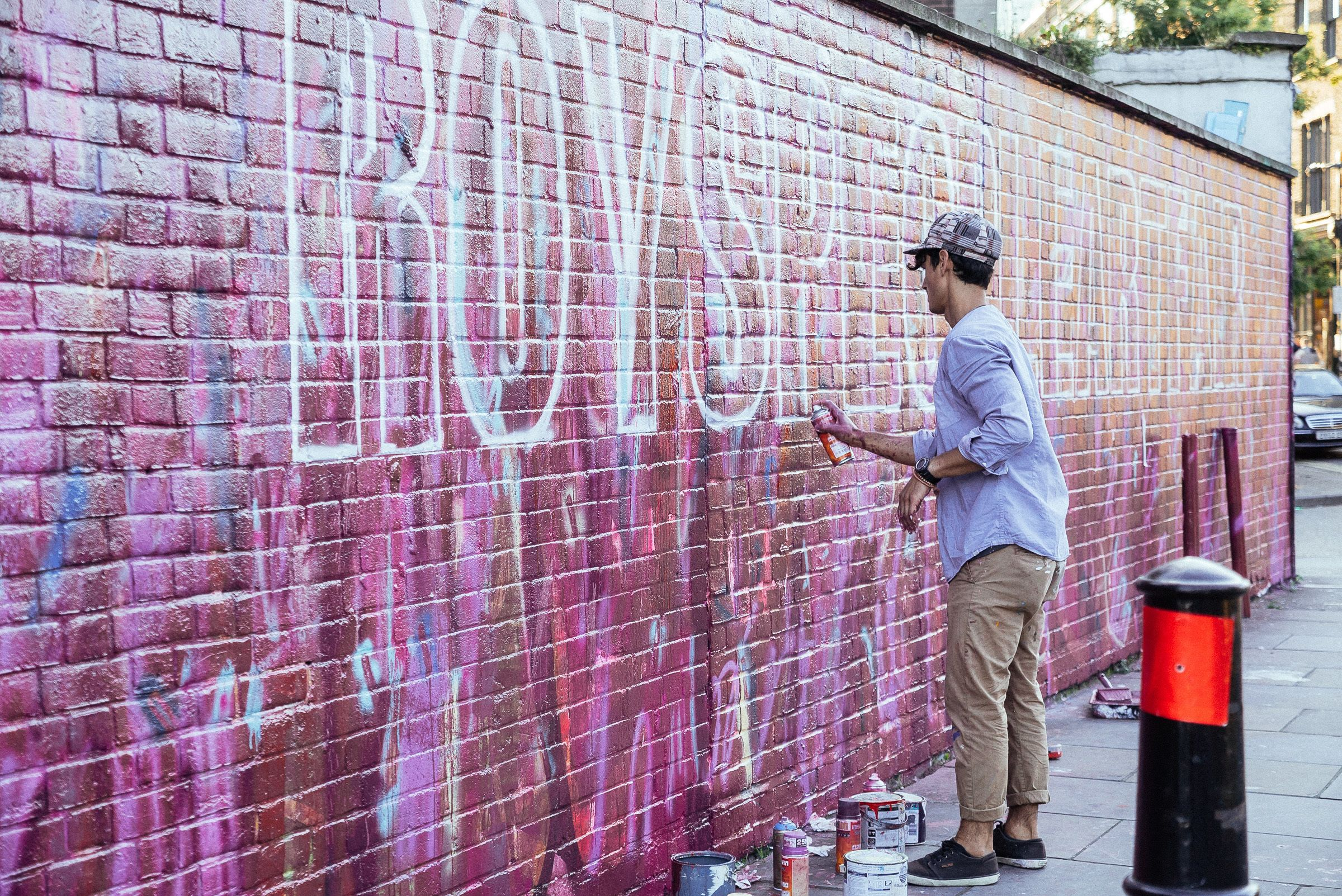Person spray painting on a wall