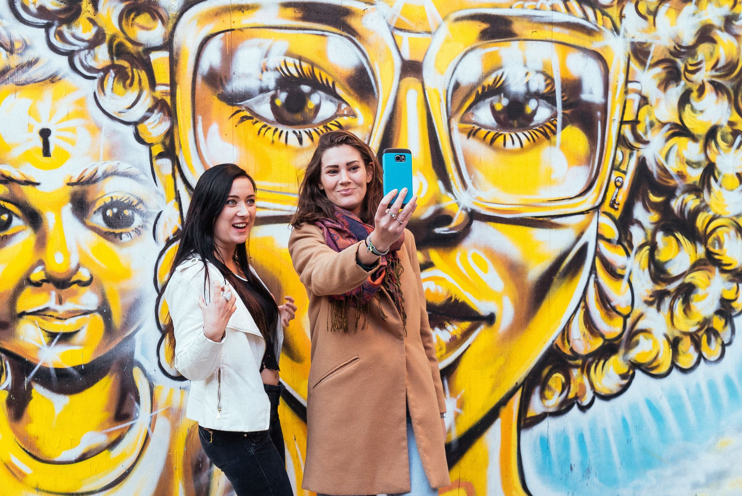 Two people taking a selfie with street art