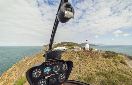 View from in a helicopter cockpit flying over Cape Cleveland