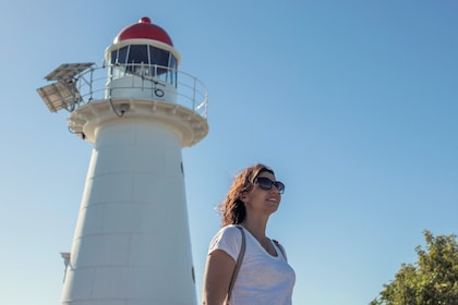 Woman stands next to lighthouse on Cape Cleveland