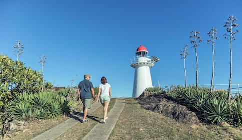 Two people walking toward a light house on Cape Cleveland