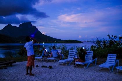 Man pointing laser at the sky at night in Bora Bora