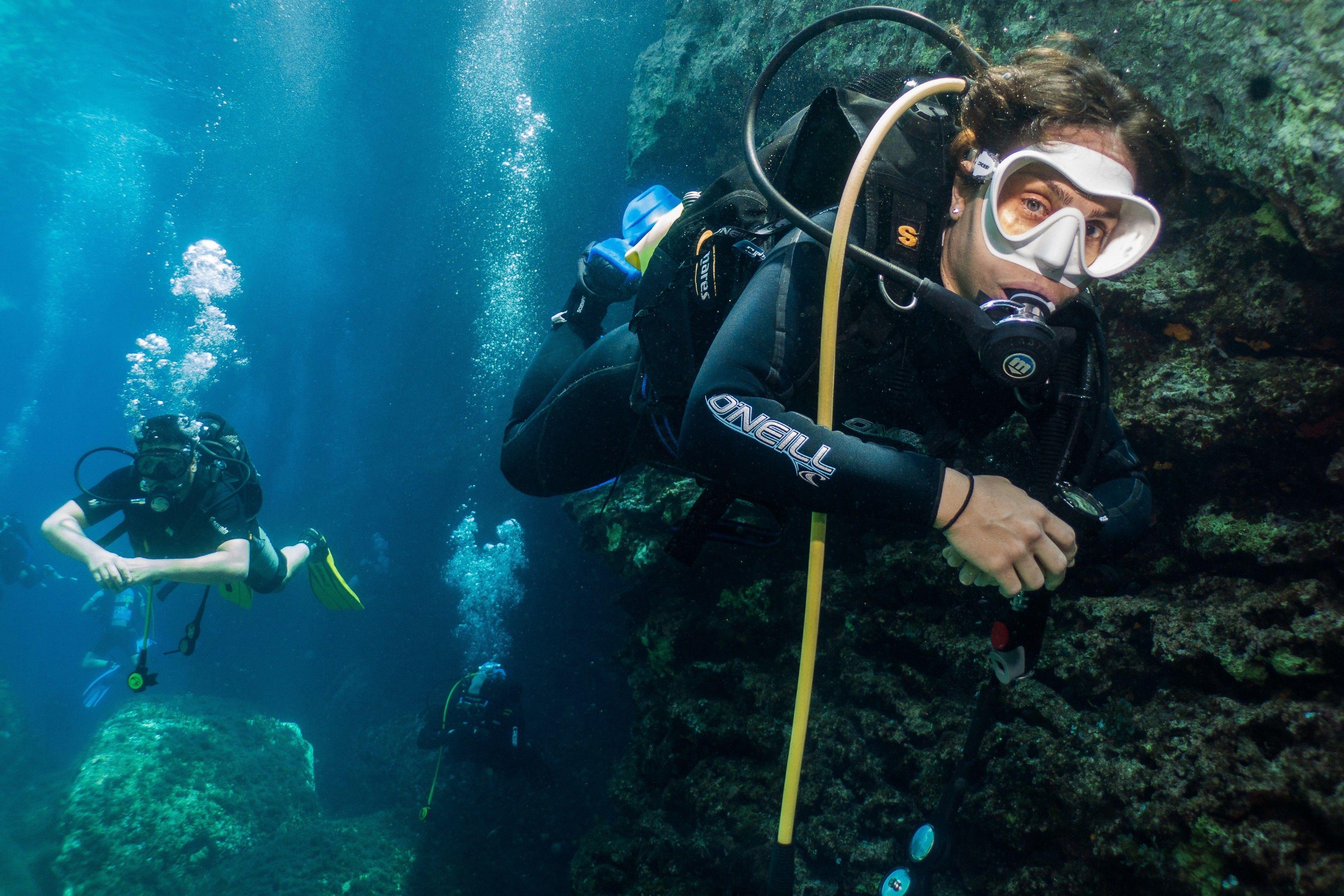 SCUBA divers swim underwater