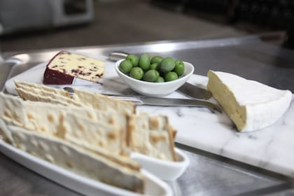 Appetizers of crackers, cheese, and olives on plates.