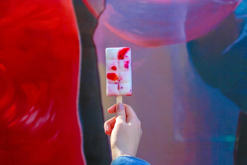 Show item 5 of 5. Woman holding up a popsicle against a colorful wall of street art in Wynwood