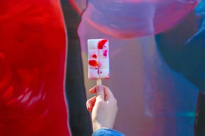 Woman holding up a popsicle against a colorful wall of street art in Wynwood