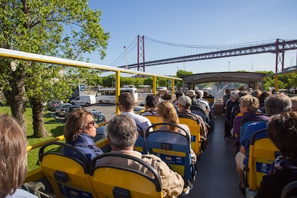 Guests sitting on the top level of the tour bus as it drives in front of a bridge in Lisbon