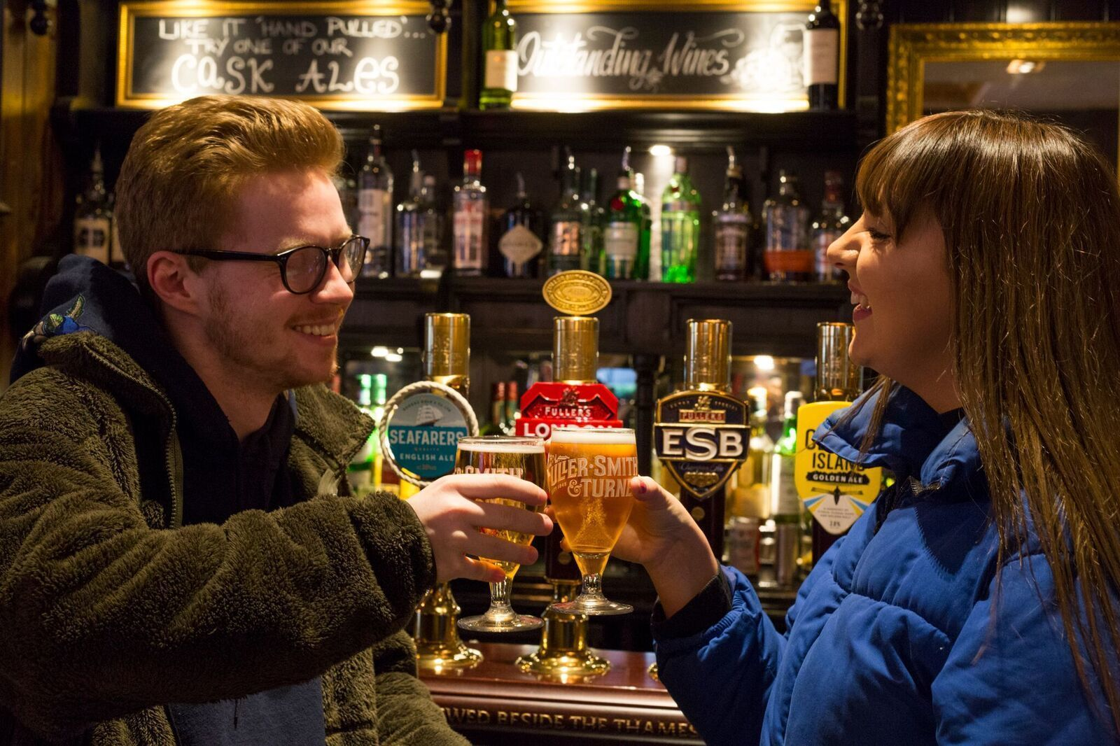 Couple drinking beer at a pub in London