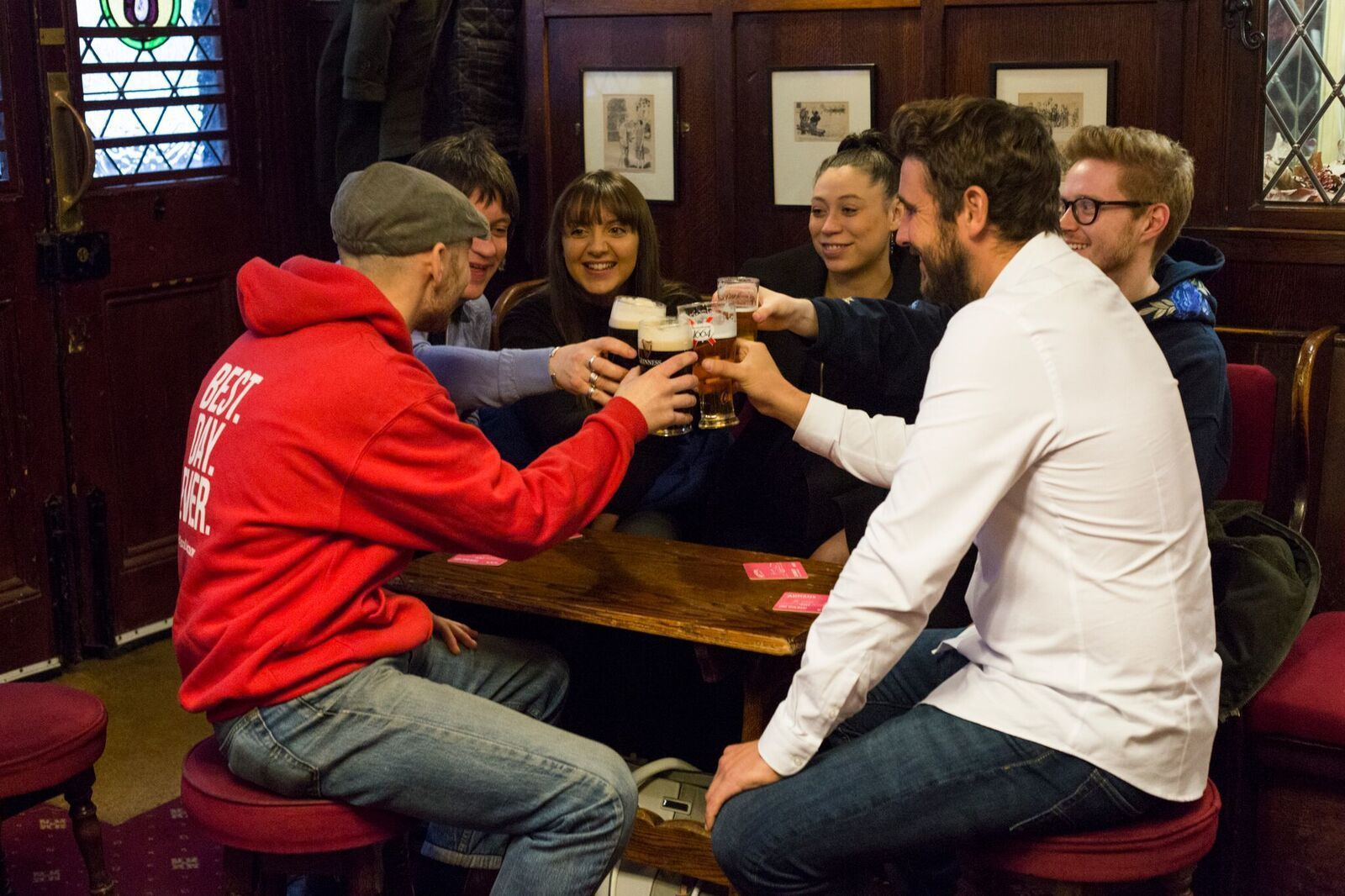 Tour group toasting with beer at a pub in London