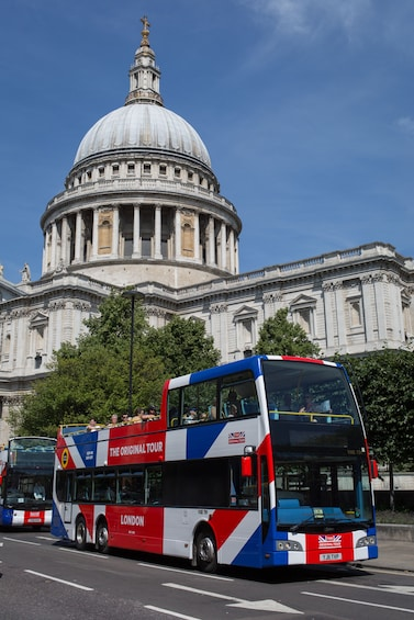 Indlæs billede 3 af 6. Double-decker tour bus driving by St Paul's Cathedral in London