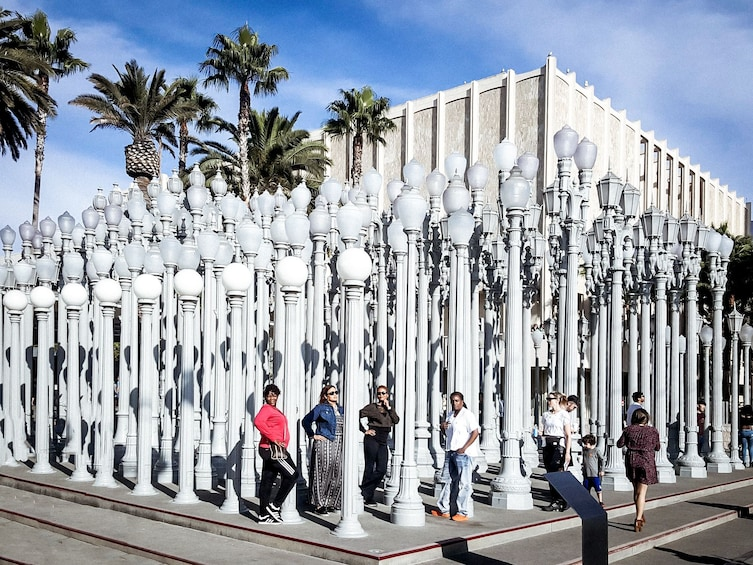 Show item 3 of 10. Tour group at a large-scale art installation of lamp posts in LA