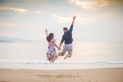 Couple jumping in the air along the beach on a photoshoot with a local and professional photographer in Maui