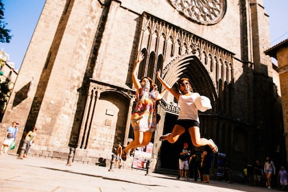 Women leaping for joy in front of church in Barcelona