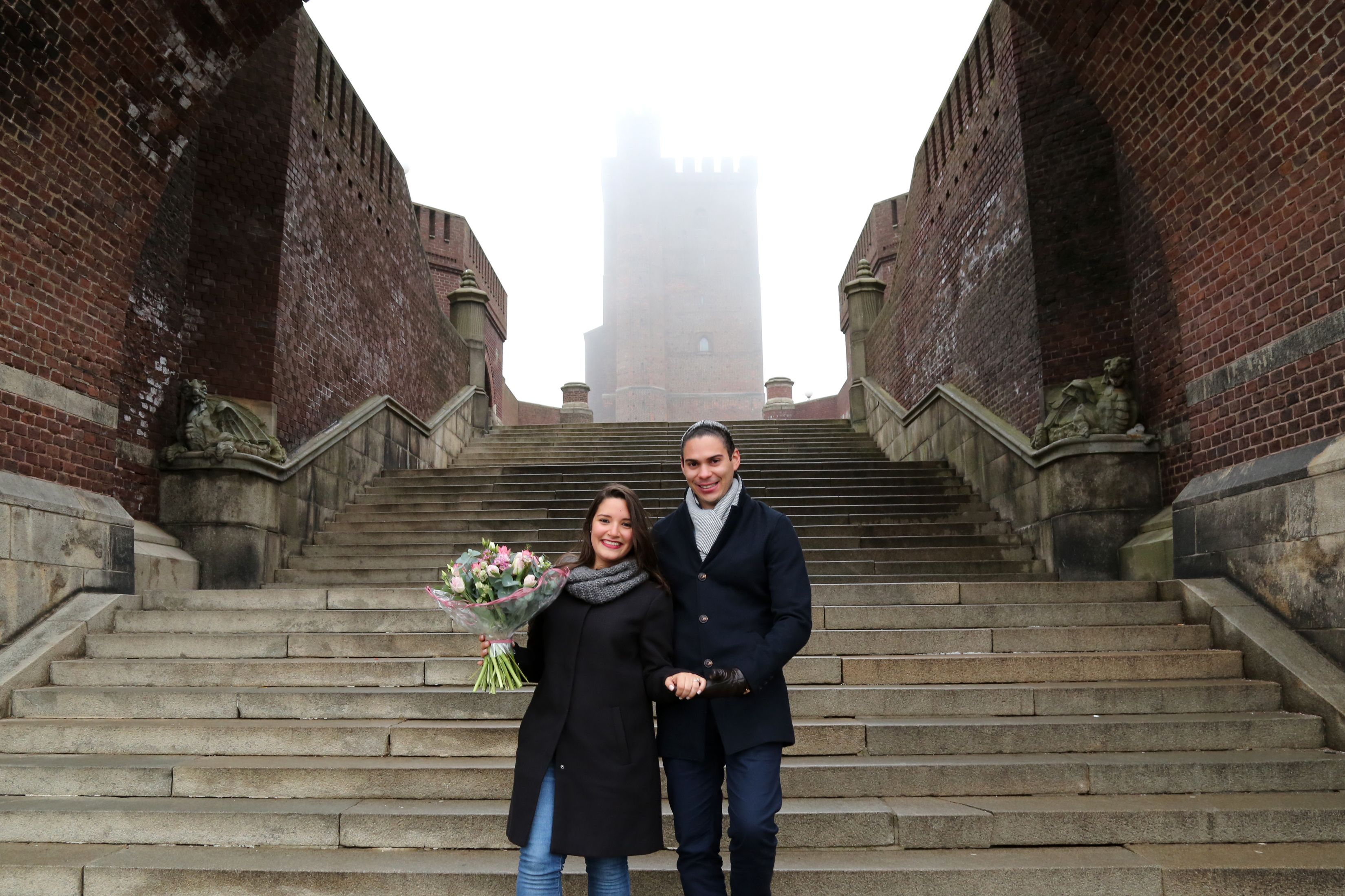 Couple poses for a photo on a foggy day in Copenhagen