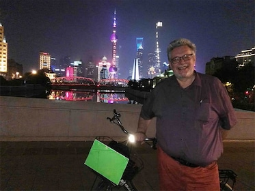 Man next to bike in front of Shanghai skyline at night