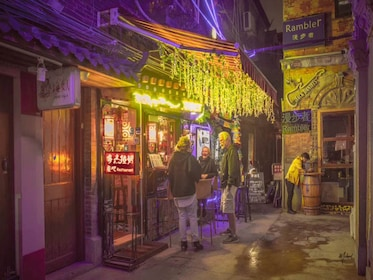 Three people stand in front of restaurant in Shanghai alley way at night