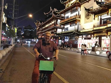 Man rides bike on street in Shanghai at night