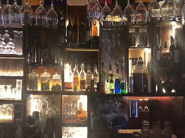 Bottles and glasses on the wall behind a bar
