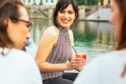 Woman holding a cocktail next to a canal in Milan